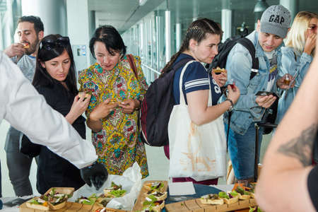 many passengers try snacks and drinks from free degustation table in Lviv airport hall 報道画像