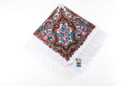 top view on flat white cotton scarf with fringe and bright floral ornament with pink, brown and blue colors lay on white background 写真素材