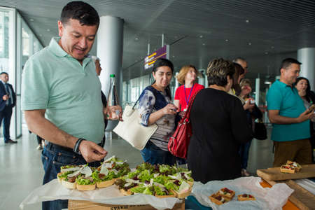 passengers try snacks and drinks from free degustation table in Lviv airport hall