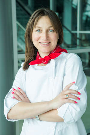 chef in white uniform smiles at camera on free degustation in Lviv airport hall