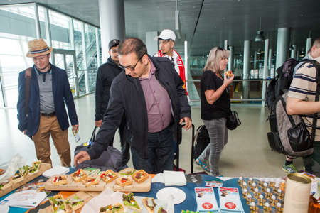 different passengers try snacks and drinks from free degustation table in Lviv airport hall 報道画像