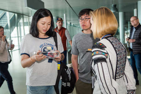closeup passengers try snacks and drinks from free degustation table in Lviv airport hall 報道画像