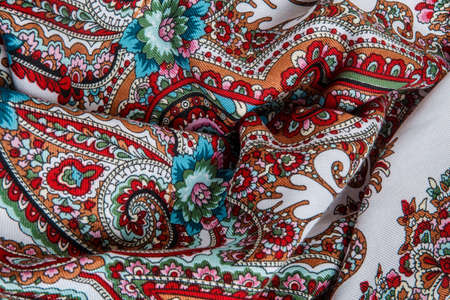 top view closeup on crumpled white cotton scarf with colorful floral ornament 写真素材