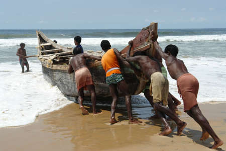 india fisherman: Indian fishermen pushing the boat Stock Photo