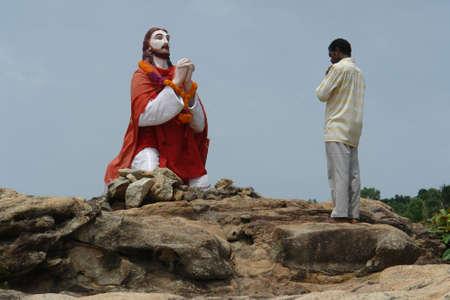 cristianismo: Un hombre est� rezando a la estatua de Jes�s