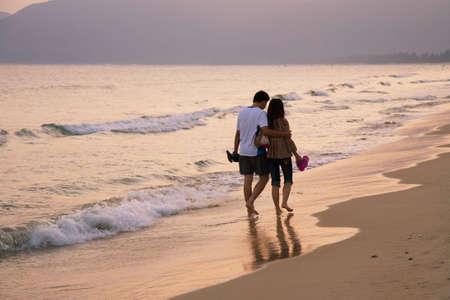 Young pair of sweethearts walking along the seashore   photo