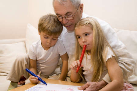 Grandpa is teaching his grandchildren to draw    Stock Photo