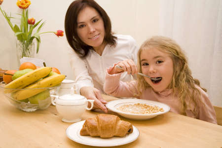 Young woman and her daughter having breakfast   photo