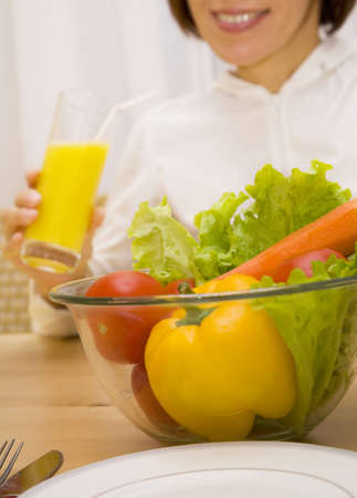 Still life of vegetables with girl drinking orange juice   photo