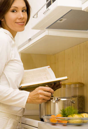 Young woman prepare meal with cook-book   Stock Photo