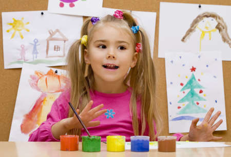 Little girl paints pictures in bright colours  photo