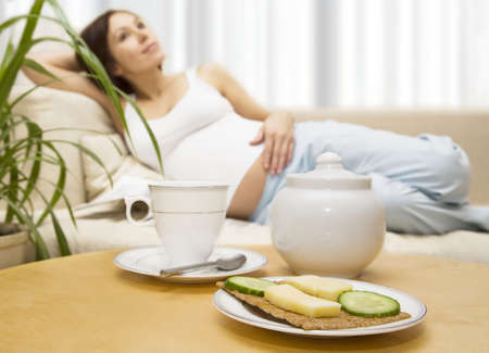 Pregnant young brunette lying on a bed before breakfast  Stock Photo