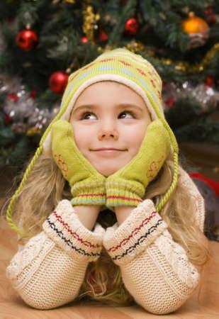 Little girl is dreaming of Christmas gift