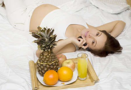 Young pregnant woman has a telephone conversation in the bed Stock Photo - 4183911