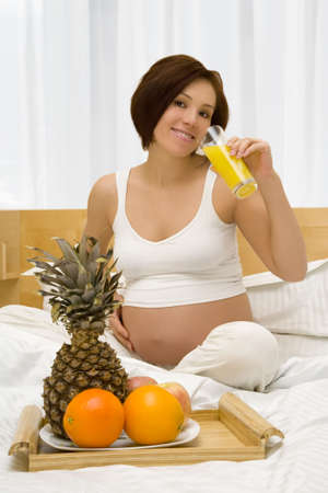 Young pregnant woman has a breakfast in the bed