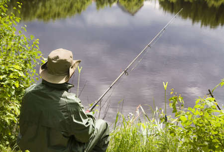 Seated senior man fishing off a shoreline Stock Photo