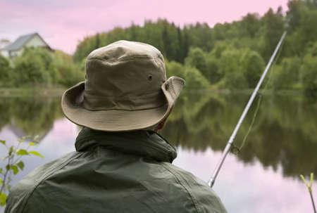 Seated senior man fishing off a shoreline photo