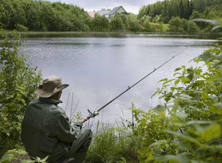 hombre pescando: Altos hombre sentado frente a una pesca costera Foto de archivo