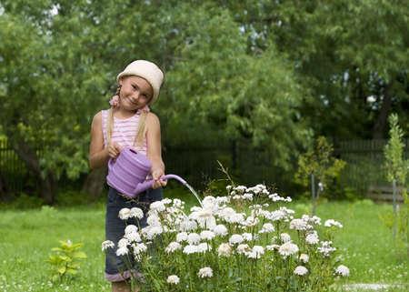 Little girl watering flowers in a garden photo