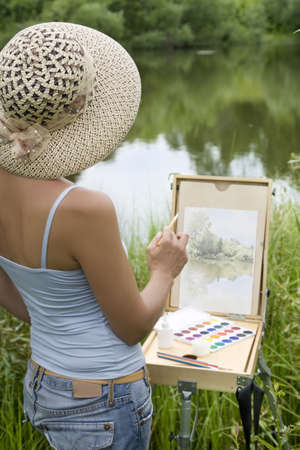 open air: Young woman painting landscape in the open air