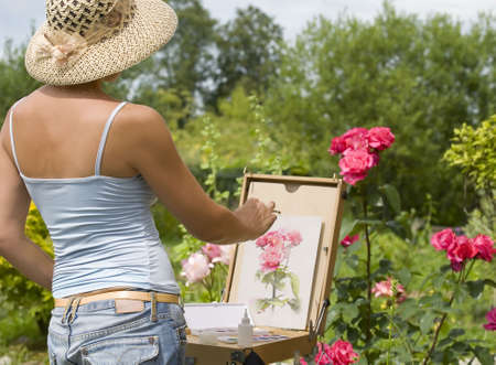 artist's canvas: Young woman painting roses in the garden   Stock Photo