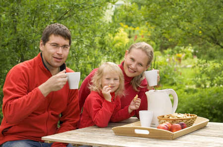 Happy family have a breakfast outdoors   photo