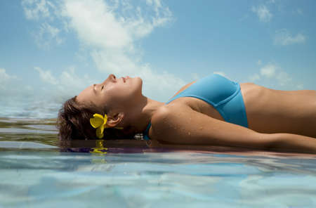 Young woman relaxing in the water against a background of the sky   photo