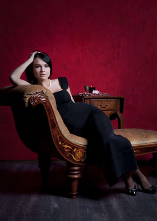 Portrait of an elegantly beautiful young woman posing on an antique couch Stock Photo