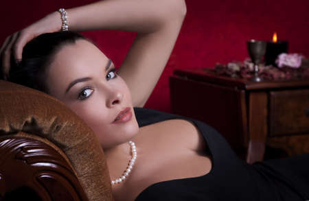 Portrait of an elegantly beautiful young woman posing on an antique couch photo
