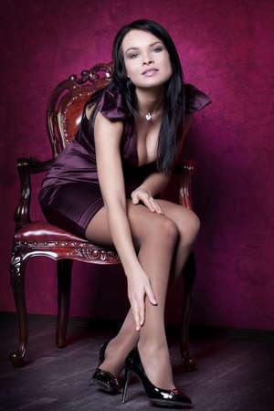 Portrait of an elegantly beautiful young woman posing on an antique chair photo