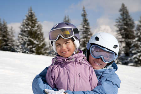 Mother and daughter posing happily against mountains Stock Photo
