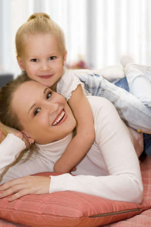 Mother and daughter posing happily. Focus on mother. photo