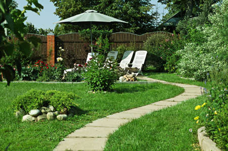 Secluded patio surrounded by flower gardens Stock Photo