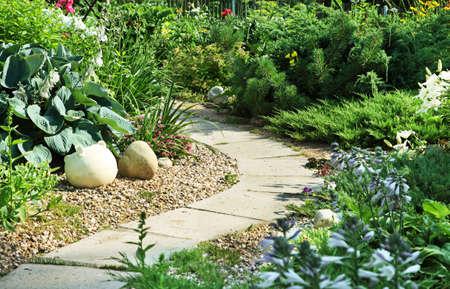 Ein Stein Gehweg windet sich durch einen ruhigen Garten
