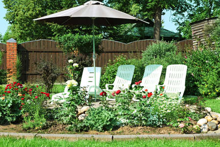 patio chairs: Secluded patio surrounded by flower gardens  Stock Photo