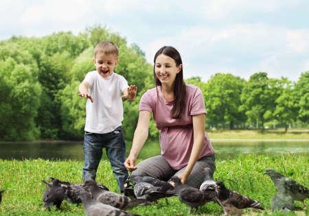 generosity: Mujer embarazada con su hijo alimentar palomas en un parque  Foto de archivo