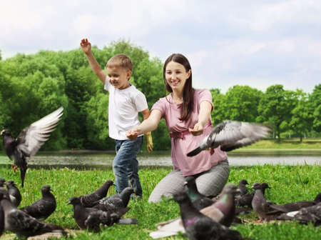 Pregnant woman with her son feeding pigeons in a park