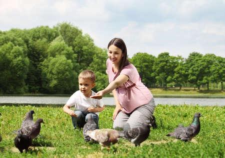 generosity: Mujer embarazada con su hijo de alimentación palomas en un parque