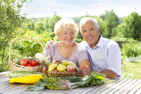 테이블에 신선한 야채와 함께 노인 부부의 초상화 스톡 콘텐츠
