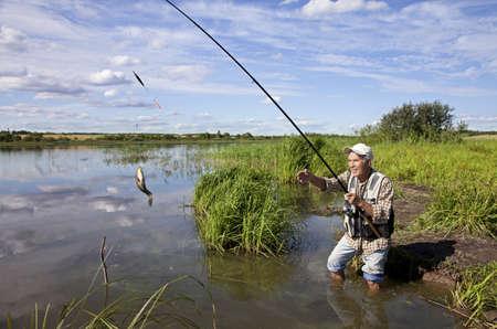 fisher animal: Senior fisherman with rod and fresh catch Stock Photo