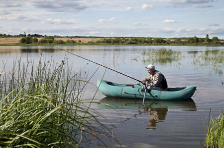 man fishing: Mature Man Fishing From a inflatable boat Stock Photo