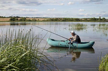 Oudere Man vissen Van een opblaasbare boot Stockfoto