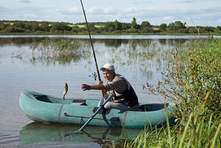 fisher: Senior fisherman with rod and fresh catch Stock Photo