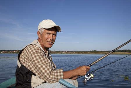 Portret van hooggeplaatste visser met hengel in zijn handen