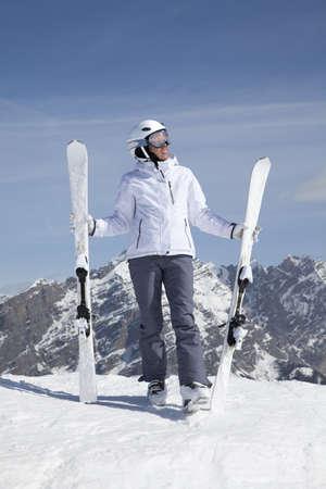 Jonge vrouw met ski's tegen de bergen