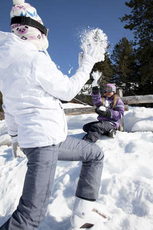 Mother and daughter playing with snow on a nice sunny winter day photo
