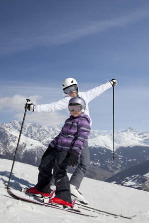 Mother and daughter posing happily against mountains photo