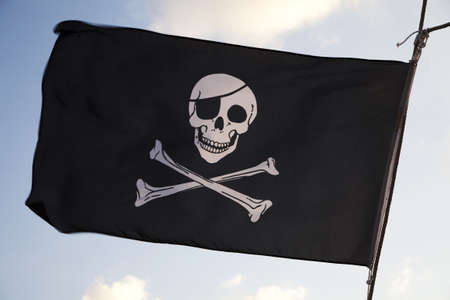 drapeau pirate: Drapeau pirate flottant au vent sur fond de ciel bleu Banque d'images