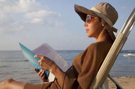 Woman reading book at beach and sitting in lawn chair photo