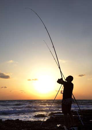 hombre pescando: Silueta de hombre que pescaba en la puesta del sol. Tiro vertical Foto de archivo